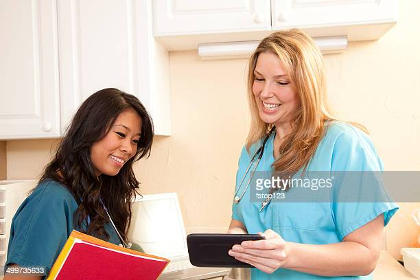 Caring female doctors review patient records. Digital tablet. Clinic.