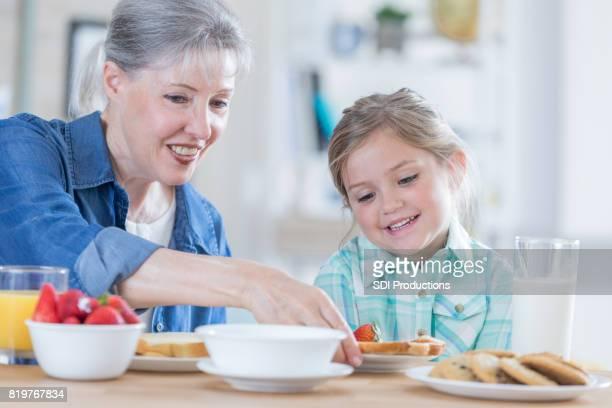 Caring grandmother gives granddaughter breakfast