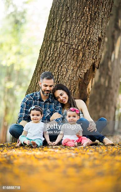 Caring latin family with twin girls sitting and smiling