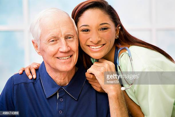 Caring, mixed-race nurse and elderly senior patient in hospital.