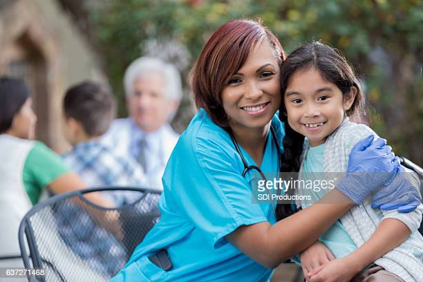 Caring nurse hugs young female Asian patient