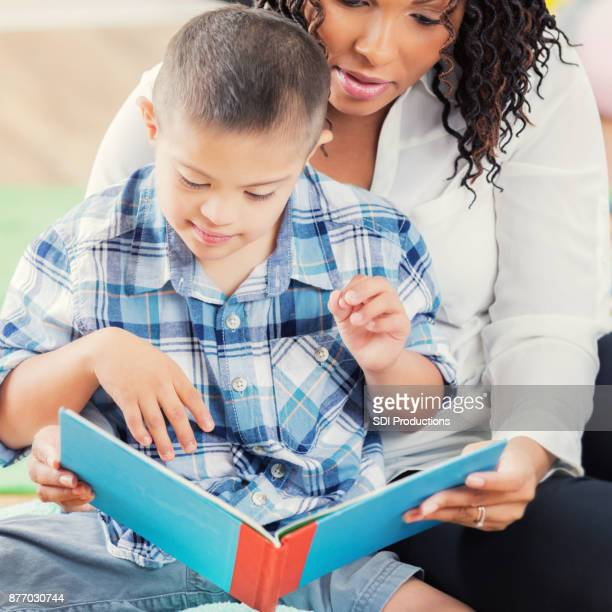 Caring preschool teacher reads book with boy with differing abilities