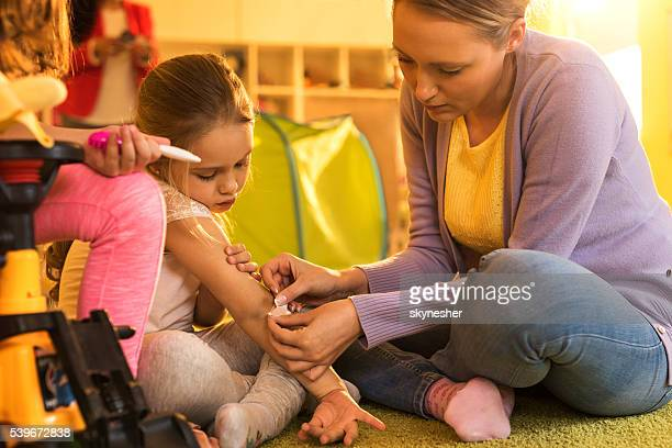 Caring teacher putting adhesive bandage in little girl's elbow.