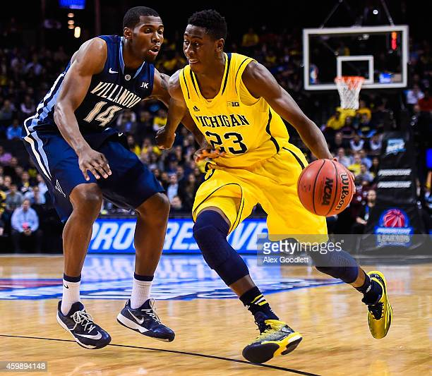 Caris LeVert of the Michigan Wolverines attempts to dribble past Darryl Reynolds of the Villanova Wildcats at the Barclays Center on November 25 2014...