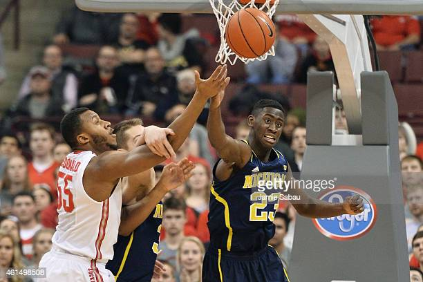 Caris LeVert of the Michigan Wolverines bats a rebound away from Trey McDonald of the Ohio State Buckeyes in the first half on January 13 2015 at...