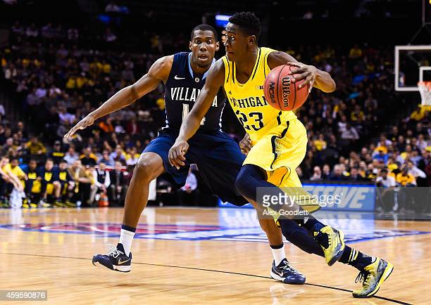 Caris LeVert of the Michigan Wolverines dribbles past Darryl Reynolds of the Villanova Wildcats in the first half at the Barclays Center on November...