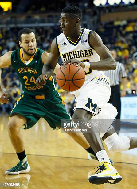 Caris LeVert of the Michigan Wolverines drives to the basket against Marcus Hall of the Northern Michigan Wildcats during the first half at Crisler...