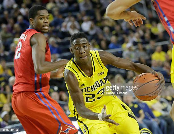 Caris LeVert of the Michigan Wolverines goes to the basket past Yanick Moreira of the Southern Methodist University Mustangs during the first half at...