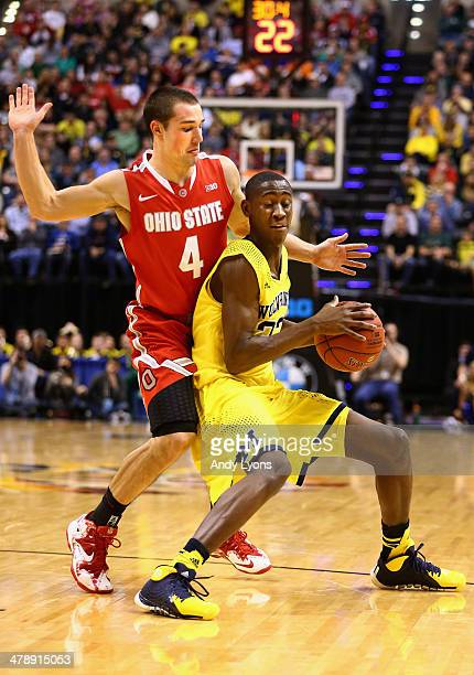 Caris LeVert of the Michigan Wolverines is pressured by Aaron Craft of the Ohio State Buckeyes during the first half of the Big Ten Basketball...