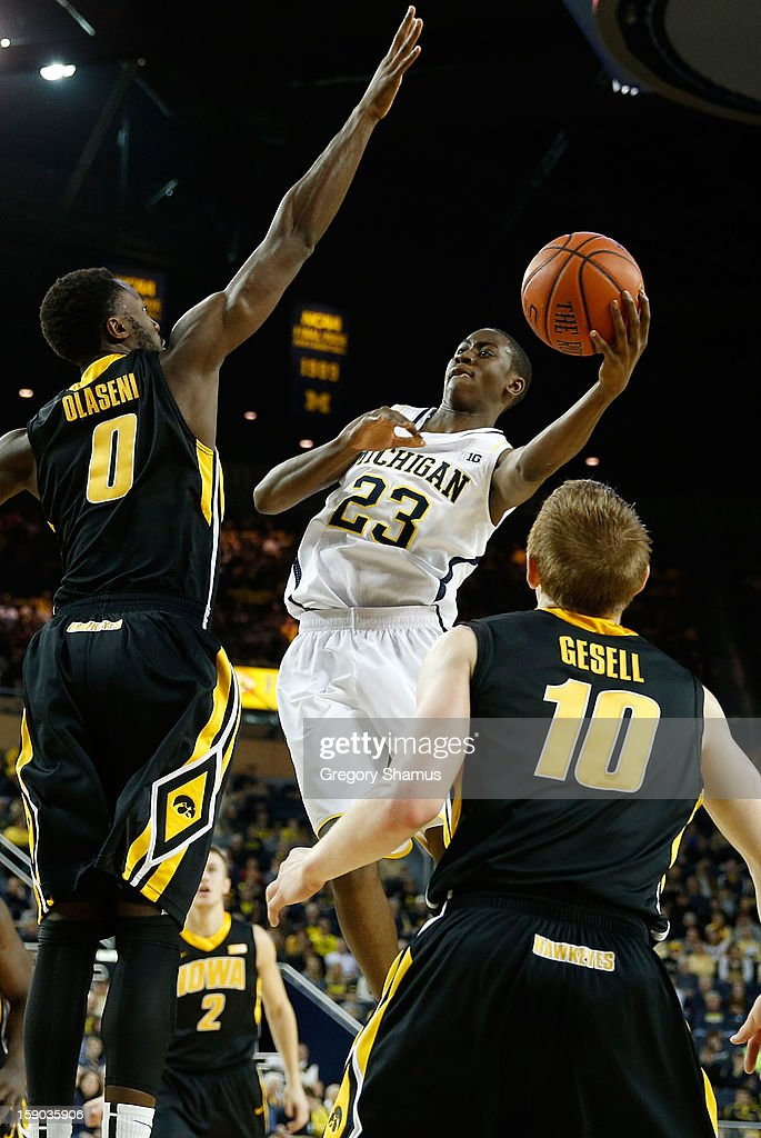 Caris LeVert #23 of the Michigan Wolverines looks to pass around the defense of Gabriel Olaseni #0 of the Iowa Hawkeyes during the first half at Crisler Center on January 6, 2013 in Ann Arbor, Michigan.