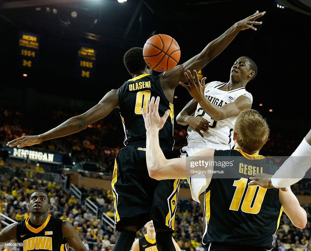 Caris LeVert #23 of the Michigan Wolverines passes around the defense of Gabriel Olaseni #0 of the Iowa Hawkeyes during the first half at Crisler Center on January 6, 2013 in Ann Arbor, Michigan. Michigan won the game 95-67.