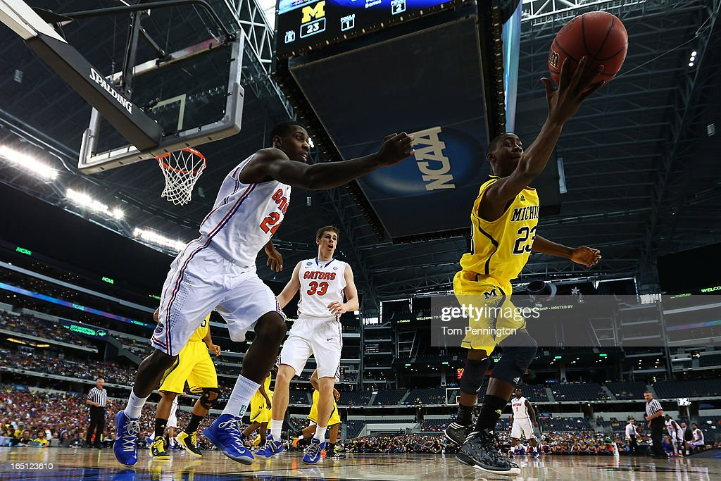Caris LeVert #23 of the Michigan Wolverines saves a ball as Casey Prather #24 of the Florida Gators defends in the first half during the South Regional Round Final of the 2013 NCAA Men's Basketball Tournament at Dallas Cowboys Stadium on March 31, 2013 in Arlington, Texas.