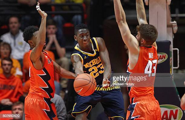 Caris LeVert of the Michigan Wolverines tries to pass the ball off as Michael Finke of the Illinois Fighting Illini defends at Memorial Stadium on...