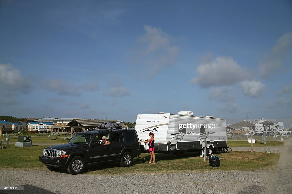 Carissa Phillips of Gettysburg Pa. directs her husband Joe Miller as he backs up to hook up their travel trailer at the KOA Capmground to comply with the mandatory evacuation orders for Hatteras Island, July 3, 2014 in Rodanthe, North Carolina. A Hurricane warning has been issued for North Carolina's Outer Banks due to approaching Tropical Storm Arthur that is expected to gain strength and become a category 1 hurricane before it passes the area.