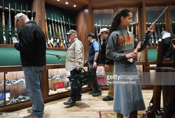 Carissa Phillips right holds a firearm in the gun library room during the opening of a new Cabela's store on Thursday March 09 2017 in Gainesville VA