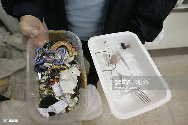 Caritas Employee shows assorted objects including a set of artificial teeth collected with the coins from the Trevi Fountains November 28 2005 in...