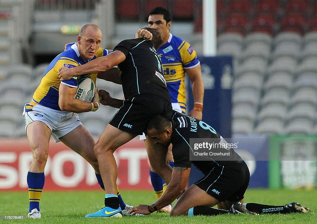 Carl Ablett of Leeds Rhinos looks to hold off London Broncos players during the Super League match between London Broncos and Leeds Rhinos at Twickenham Stoop on August 01, 2013 in London, England.