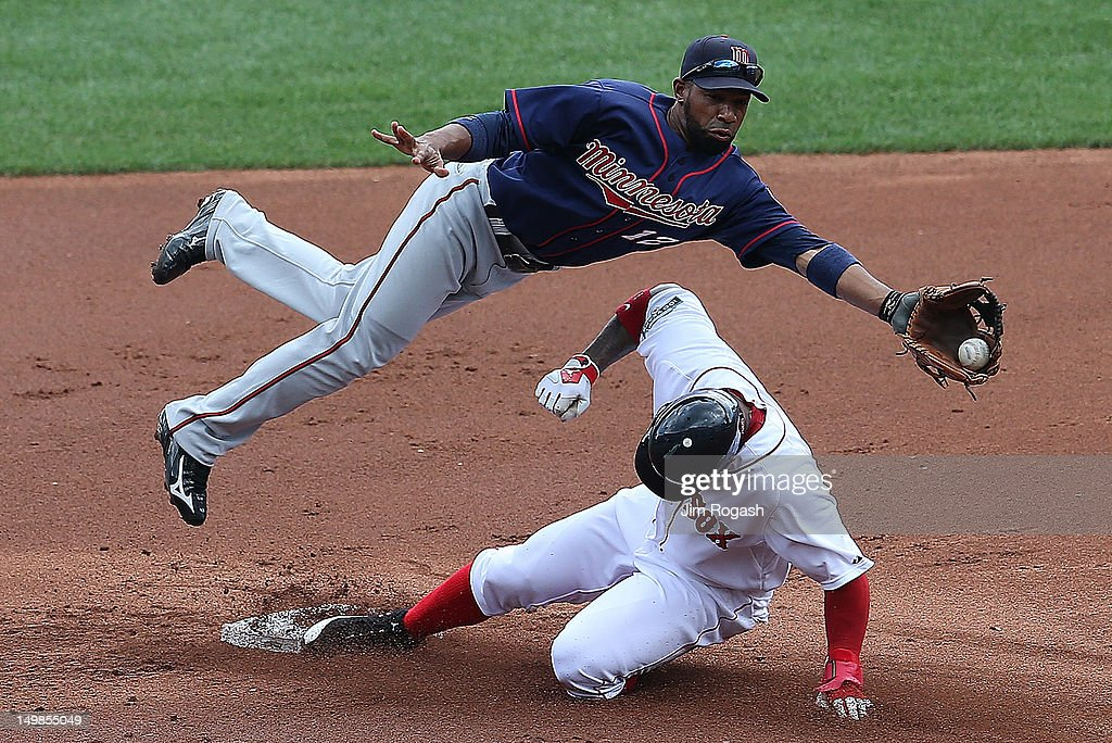 Carl Crawford of the Boston Red Sox steals second base as Alexi Casilla of the Minnesota Twins fields a high throw in the first inning at Fenway Park...