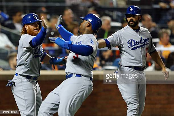 Carl Crawford of the Los Angeles Dodgers celebrates with teammates Andre Ethier and Justin Turner after scoring off of Yasmani Grandal single to...