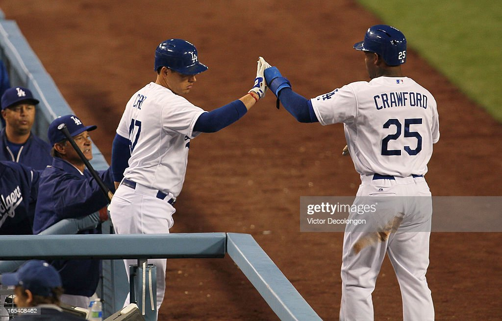 Carl Crawford #25 of the Los Angeles Dodgers gets a high-five from teammate Luis Cruz #47 after scoring on a passed ball in the first inning against the San Francisco Giants during the MLB game at Dodger Stadium on April 3, 2013 in Los Angeles, California.