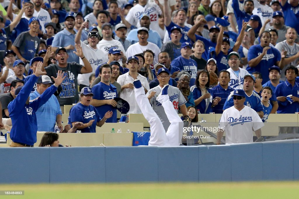 <a gi-track='captionPersonalityLinkClicked' href=/galleries/search?phrase=Carl+Crawford&family=editorial&specificpeople=208074 ng-click='$event.stopPropagation()'>Carl Crawford</a> #25 of the Los Angeles Dodgers makes a catch on a ball hit by Brian McCann #16 of the Atlanta Braves and falls into the stands in the eighth inning during Game Three of the National League Division Series at Dodger Stadium on October 6, 2013 in Los Angeles, California.