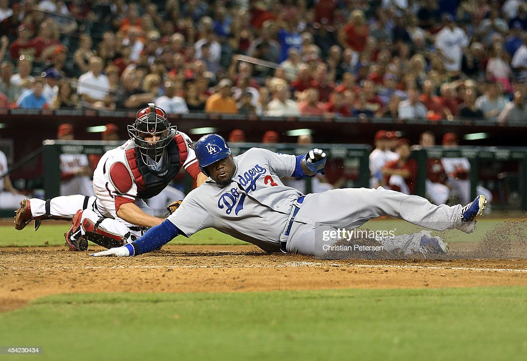 Carl Crawford of the Los Angeles Dodgers safely slides in to score a run past the tag from catcher Miguel Montero of the Arizona Diamondbacks during...