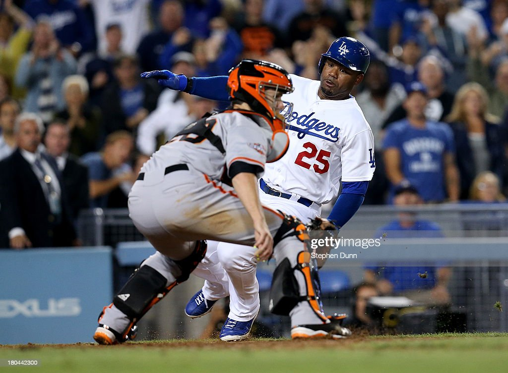 Carl Crawford #25 of the Los Angeles Dodgers slides past catcher Buster Posey #28 of the San Francisco Giants to score the winning run on a walk off single by Adrian Gonzalez in the tenth inning at Dodger Stadium on September 12, 2013 in Los Angeles, California. The Dodgers won 3-2 in ten innings.