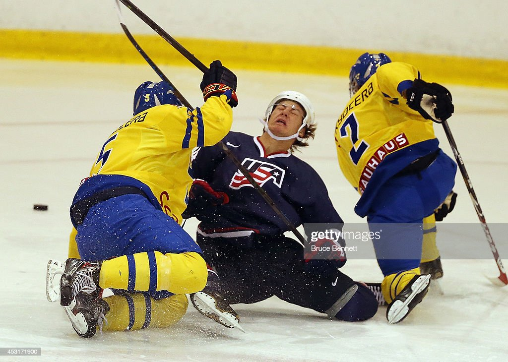 Carl Dahlstrom # (L) and Sebastian Aho #2 (R) of Team Sweden combine to take down <a gi-track='captionPersonalityLinkClicked' href=/galleries/search?phrase=John+Hayden+-+Ice+Hockey+Player&family=editorial&specificpeople=15212509 ng-click='$event.stopPropagation()'>John Hayden</a> #14 of USA Blue during the 2014 USA Hockey Junior Evaluation Camp at the Lake Placid Olympic Center on August 4, 2014 in Lake Placid, New York.