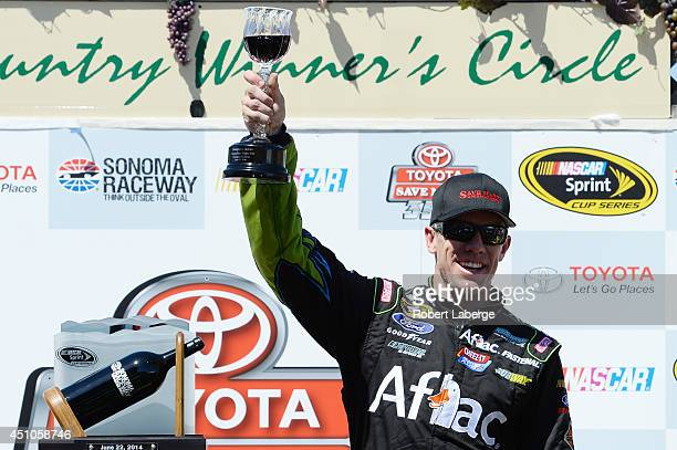 Carl Edwards driver of the Aflac Ford celebrates in victory lane after winning the NASCAR Sprint Cup Series Toyota/Save Mart 350 at Sonoma Raceway on...