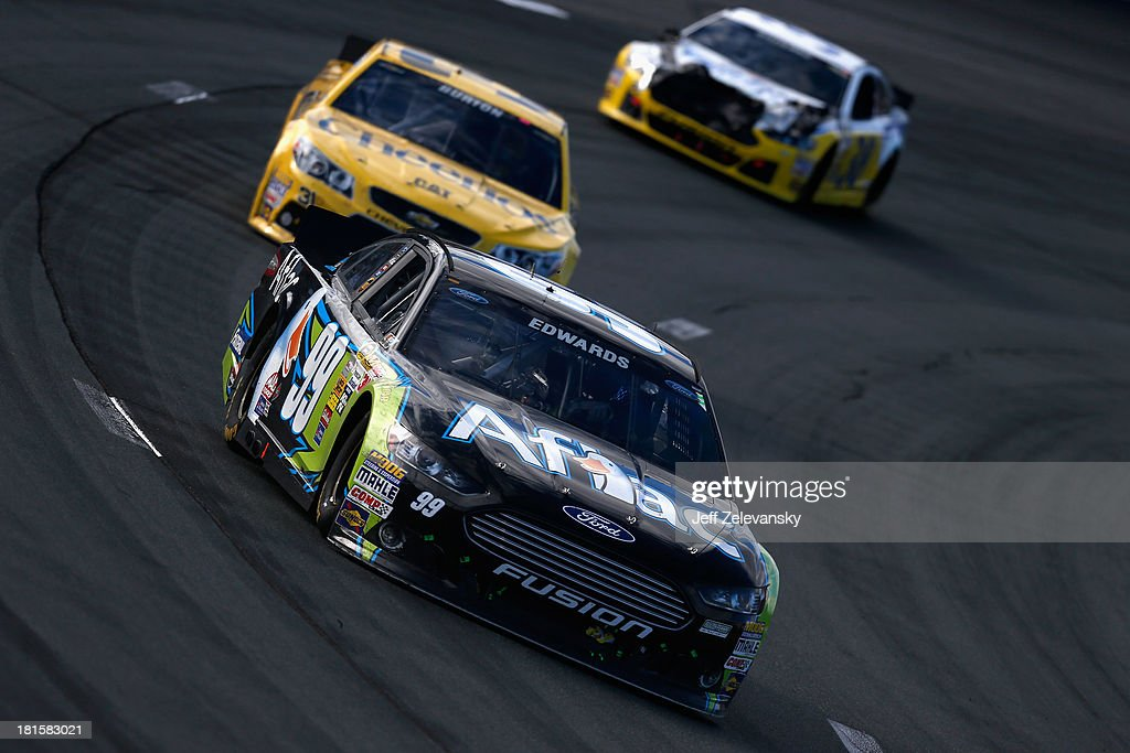 Carl Edwards, driver of the #99 Aflac Ford, leads a pack of cars during the NASCAR Sprint Cup Series Sylvania 300 at New Hampshire Motor Speedway on September 22, 2013 in Loudon, New Hampshire.