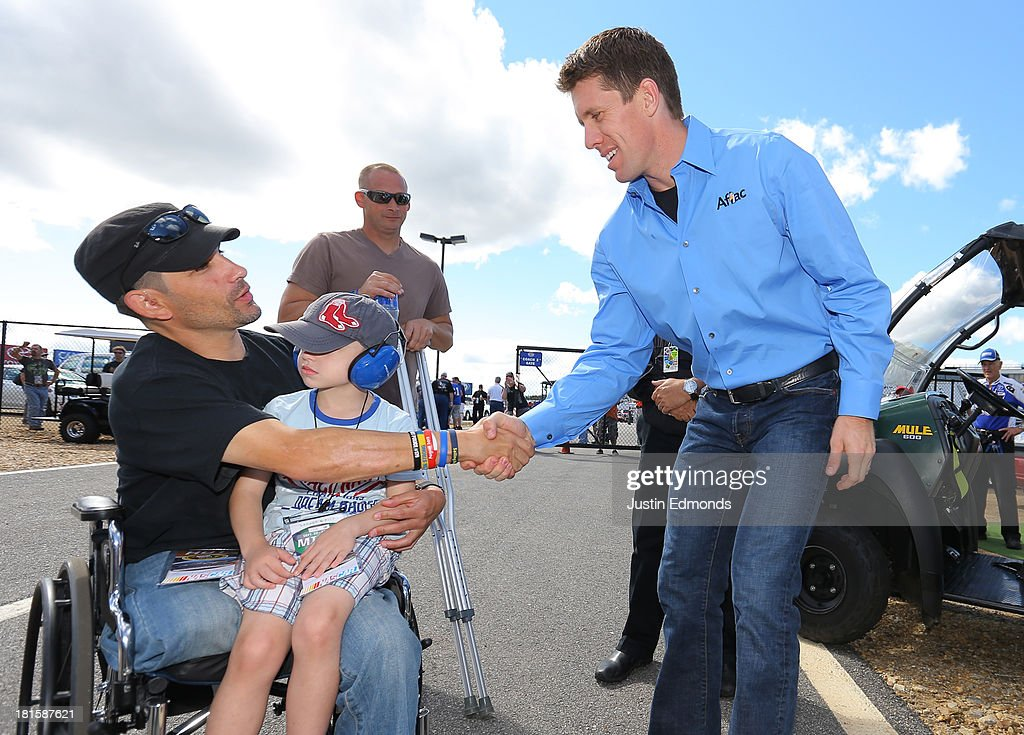 Carl Edwards (R), driver of the #99 Aflac Ford, shakes hands with Marc Fucarile (L), who was the last Boston Marathon bombing survivor discharged from the hospital, prior to the NASCAR Sprint Cup Series Sylvania 300 at New Hampshire Motor Speedway on September 22, 2013 in Loudon, New Hampshire.