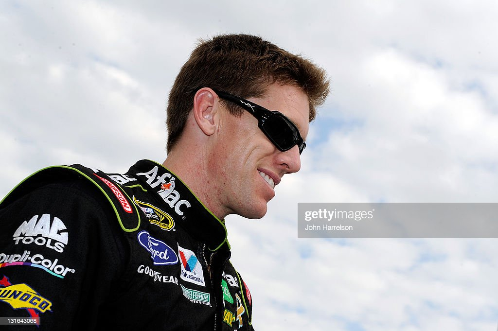 Carl Edwards, driver of the #99 Aflac Ford, smiles as he stands on the grid prior to the start of the NASCAR Sprint Cup Series AAA Texas 500 at Texas Motor Speedway on November 6, 2011 in Fort Worth, Texas.