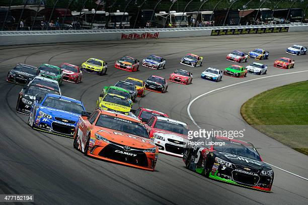 Carl Edwards driver of the ARRIS Toyota and Kasey Kahne driver of the Great Clips Chevrolet lead a pack of cars during the NASCAR Sprint Cup Series...