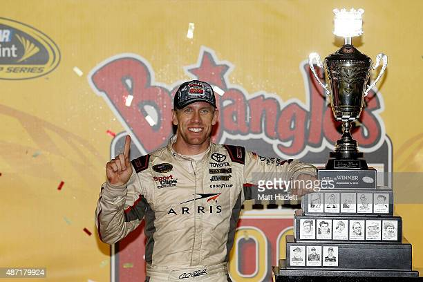 Carl Edwards driver of the ARRIS Toyota poses with the winner's trophy in Victory Lane after winning the NASCAR Sprint Cup Series Bojangles' Southern...