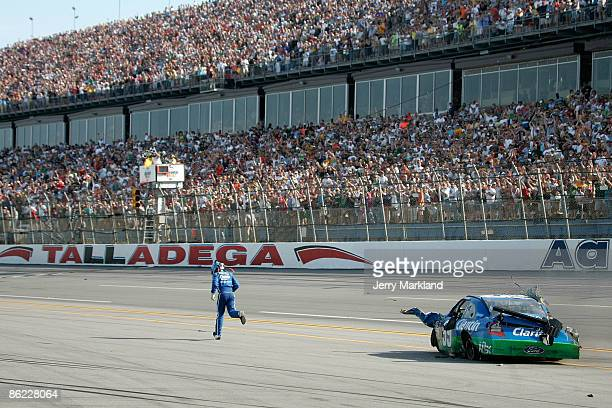 Carl Edwards driver of the Claritin Ford runs to the finish line after suffering damage at the conclusion of the NASCAR Sprint Cup Series Aaron's 499...