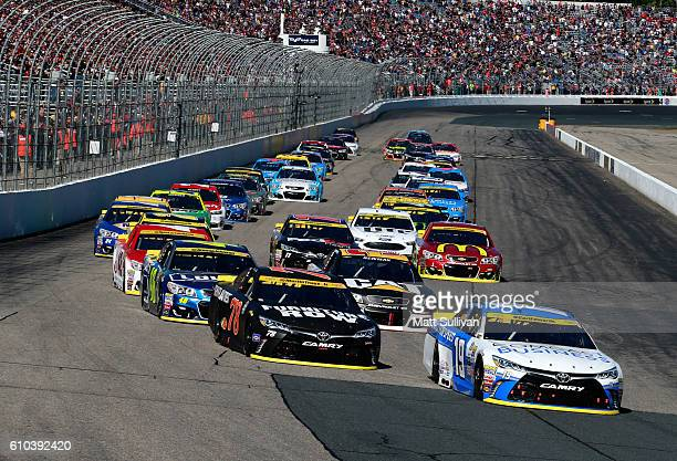 Carl Edwards driver of the Comcast Business Toyota leads the field past the green flag to start the NASCAR Sprint Cup Series Bad Boy Off Road 300 at...