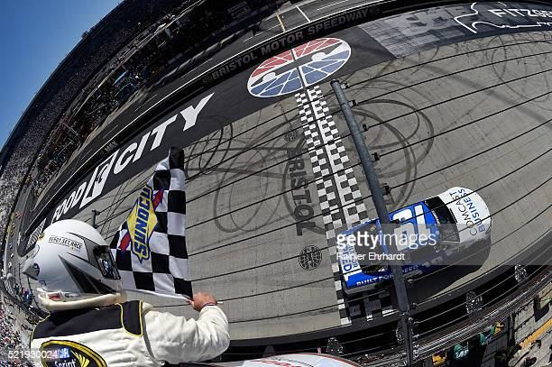 Carl Edwards driver of the Comcast Business Toyota takes the checkered flag to win the NASCAR Sprint Cup Series Food City 500 at Bristol Motor...