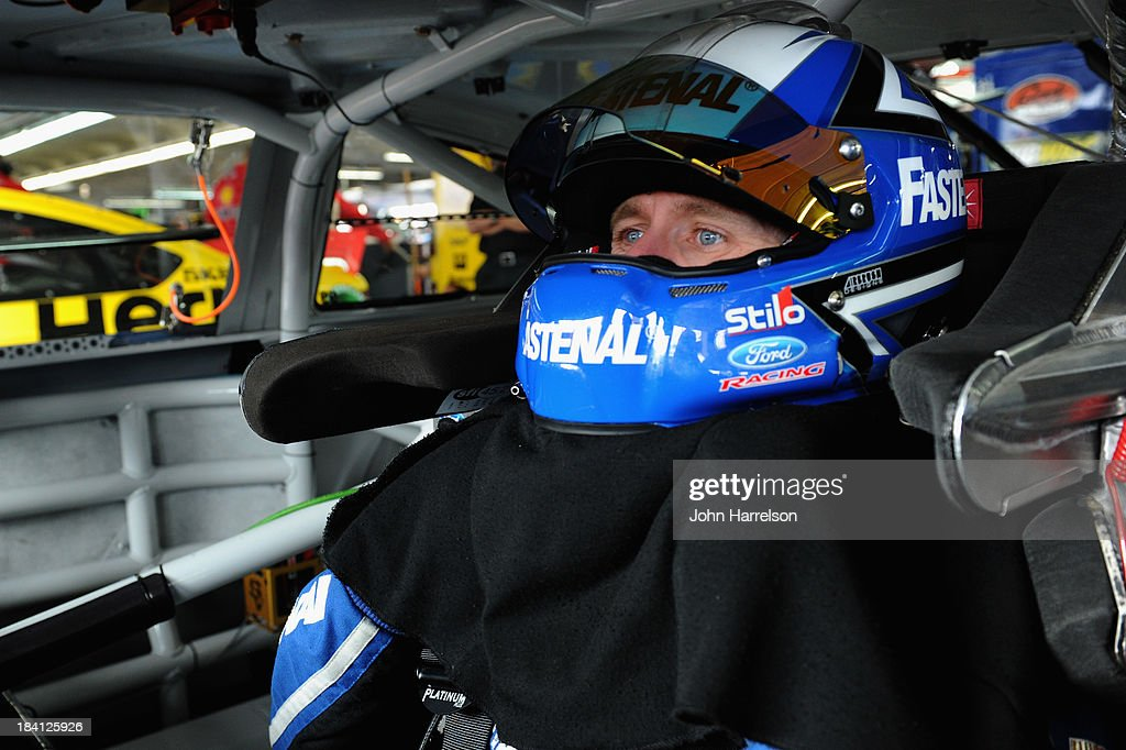 Carl Edwards, driver of the #99 Fastenal Ford, adjusts the equipment in his car during practice for the NASCAR Sprint Cup Series Bank of America 500 at Charlotte Motor Speedway on October 11, 2013 in Concord, North Carolina.