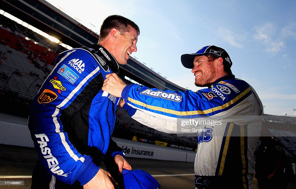 Carl Edwards, driver of the #99 Fastenal Ford, and Brian Vickers, driver of the #55 Aaron's Dream Machine Toyota, talk on the grid during qualifying for the NASCAR Sprint Cup Series IRWIN Tools Night Race at Bristol Motor Speedway on August 23, 2013 in Bristol, Tennessee.