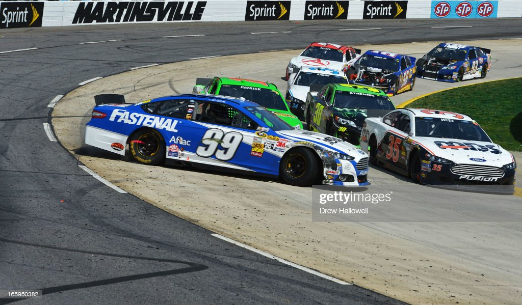 Carl Edwards, driver of the #99 Fastenal Ford, and Danica Patrick, driver of the #10 GoDaddy.com Chevrolet, are involved in an incident during the NASCAR Sprint Cup Series STP Gas Booster 500 on April 7, 2013 at Martinsville Speedway in Ridgeway, Virginia.
