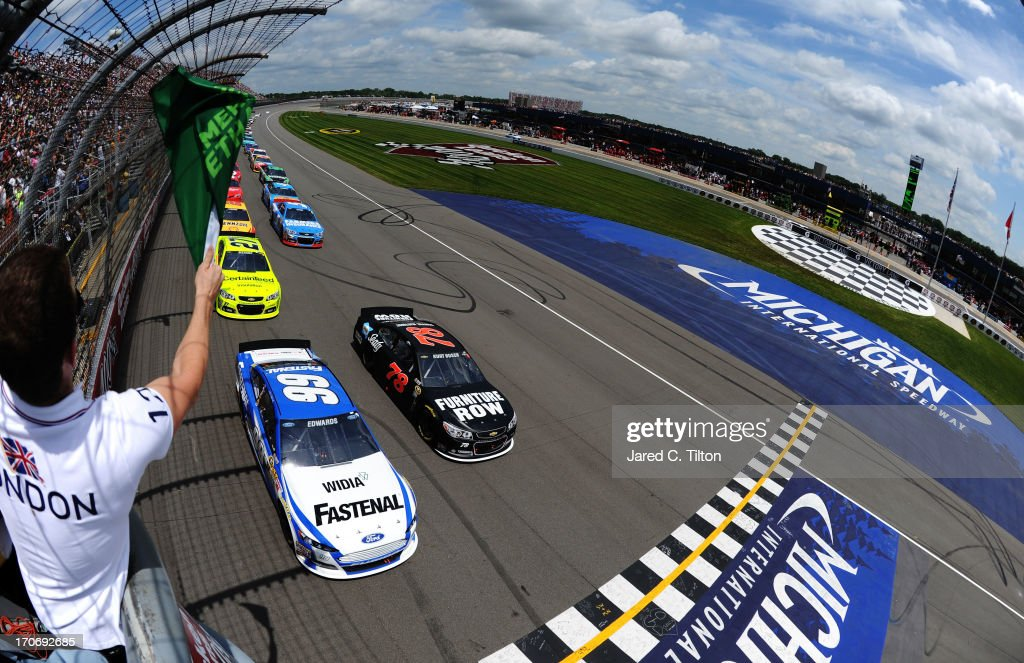 <a gi-track='captionPersonalityLinkClicked' href=/galleries/search?phrase=Carl+Edwards&family=editorial&specificpeople=193803 ng-click='$event.stopPropagation()'>Carl Edwards</a>, driver of the #99 Fastenal Ford, and <a gi-track='captionPersonalityLinkClicked' href=/galleries/search?phrase=Kurt+Busch&family=editorial&specificpeople=201728 ng-click='$event.stopPropagation()'>Kurt Busch</a>, driver of the #78 Furniture Row/Sealy Chevrolet, lead the field to the green flag to start the NASCAR Sprint Cup Series Quicken Loans 400 at Michigan International Speedway on June 16, 2013 in Brooklyn, Michigan.