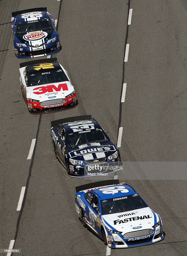Carl Edwards, driver of the #99 Fastenal Ford, leads Jimmie Johnson, driver of the #48 Lowe's Chevrolet, Greg Biffle, driver of the #16 3M Ford, and Travis Kvapil, driver of the #93 Burger King/Dr. Pepper Toyota, during the NASCAR Sprint Cup Series STP Gas Booster 500 on April 7, 2013 at Martinsville Speedway in Ridgeway, Virginia.