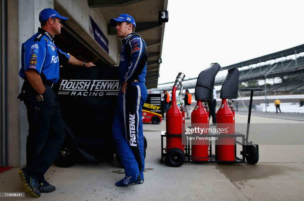 Carl Edwards, driver of the #99 Fastenal Ford, talks with a crew member during practice for the NASCAR Sprint Cup Series Samuel Deeds 400 At The Brickyard at Indianapolis Motor Speedway on July 27, 2013 in Indianapolis, Indiana.