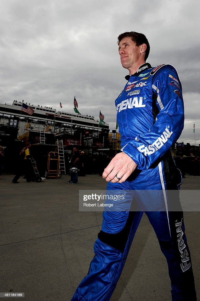 Carl Edwards, driver of the #99 Fastenal Ford, walks through the garage area during qualifying for the NASCAR Sprint Cup Series STP 500 at Martinsville Speedway on March 28, 2014 in Martinsville, Virginia.
