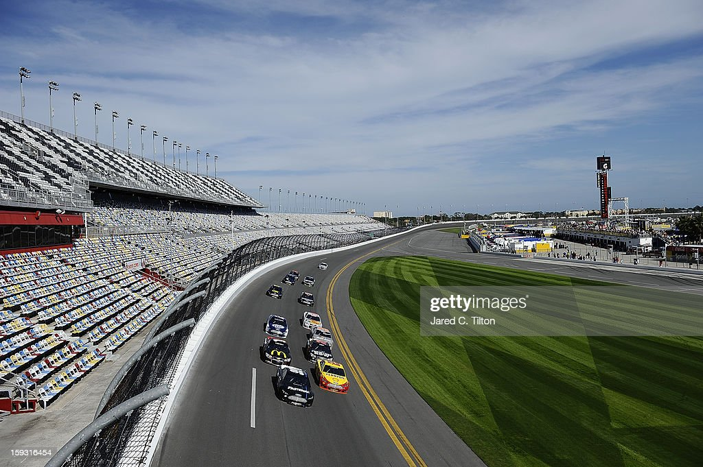 Carl Edwards, driver of the #99 Ford, and Joey Logano, driver of the #22 Ford, lead a pack of cars through the tri-oval during NASCAR Sprint Cup Series Preseason Thunder testing at Daytona International Speedway on January 11, 2013 in Daytona Beach, Florida.