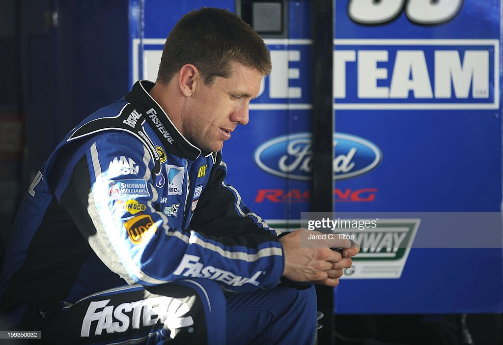 Carl Edwards, driver of the #99 Ford, uses his smart phone in the garage area during NASCAR Sprint Cup Series Preseason Thunder testing at Daytona International Speedway on January 12, 2013 in Daytona Beach, Florida.