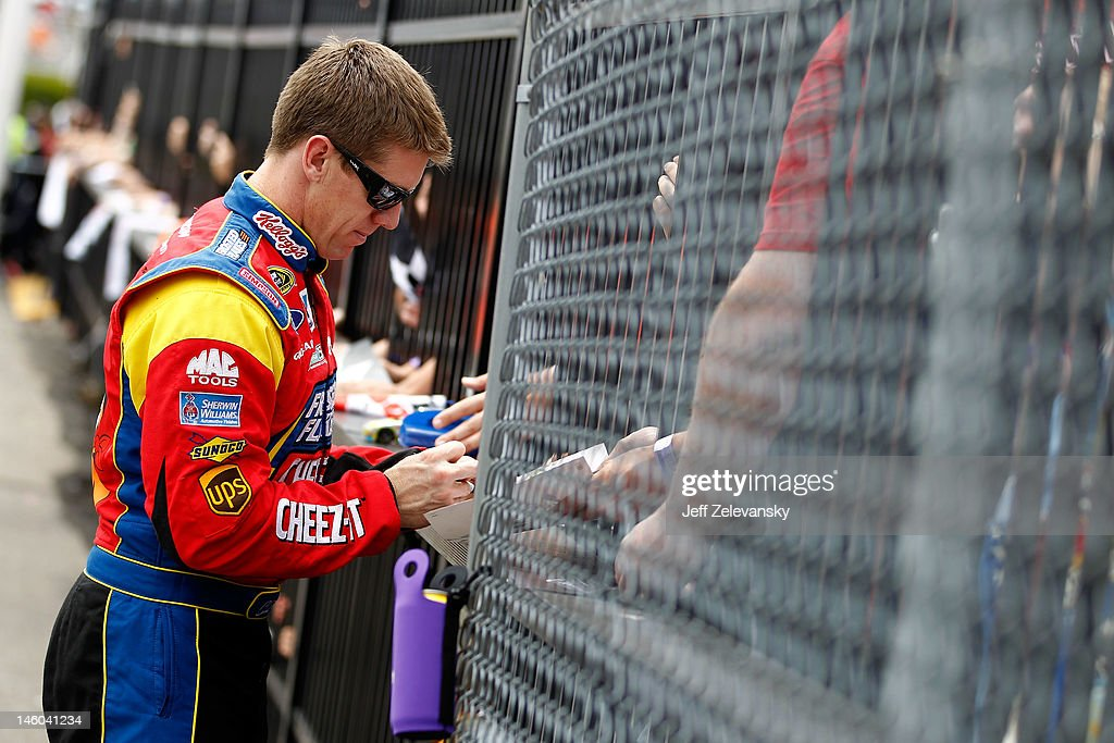 <a gi-track='captionPersonalityLinkClicked' href=/galleries/search?phrase=Carl+Edwards+-+Racecar+Driver&family=editorial&specificpeople=193803 ng-click='$event.stopPropagation()'>Carl Edwards</a>, driver of the #99 Kellogg's Ford, signs autographs during qualifying for the NASCAR Sprint Cup Series Pocono 400 presented by #NASCAR at Pocono Raceway on June 9, 2012 in Long Pond, Pennsylvania.