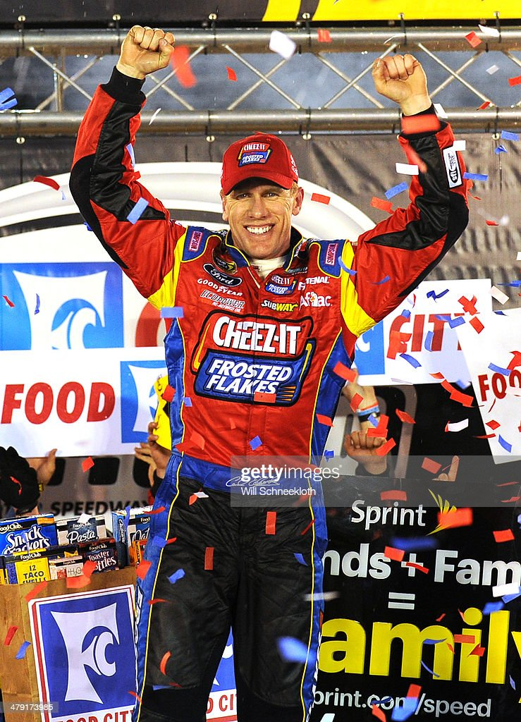 Carl Edwards driver of the Kellogg's / Frosted Flakes Ford celebrates in Victory Lane after taking the checkered flag under caution to win the NASCAR...