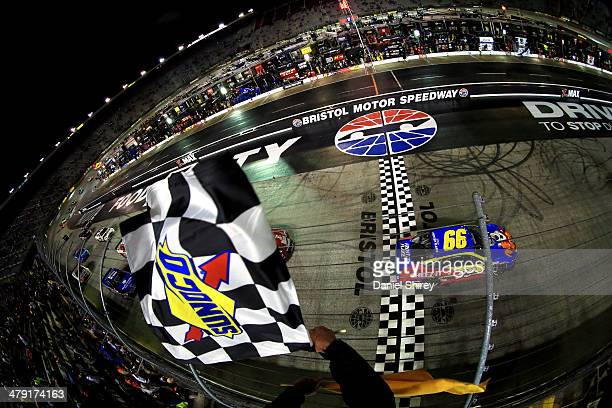Carl Edwards driver of the Kellogg's/Frosted Flakes Ford takes the checkered flag as he crosses the finish line under caution to win the NASCAR...