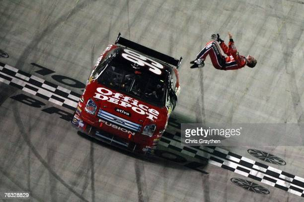 Carl Edwards driver of the Office Depot Ford celebrates with a backflip out of his car after winning the NASCAR Nextel Cup Series Sharpie 500 at...
